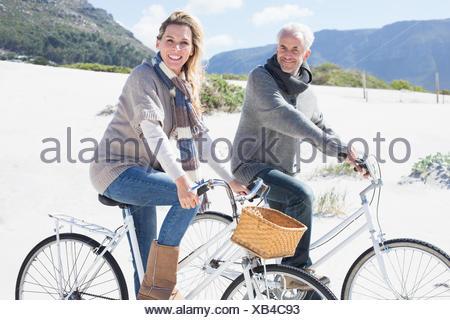 Despreocupada par ir en un paseo en bicicleta en la playa, sonriendo a la cámara