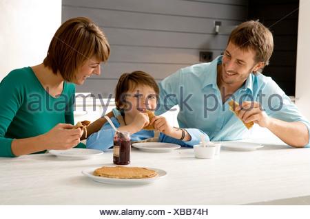Mitad hombre adulto y una mujer joven desayunando con su hijo Foto de stock