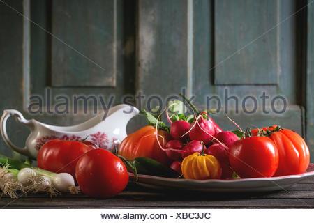 Montón de coloridos vegetales frescos maduros los tomates, ají, cebolla verde y montón de rábano en vintage placa y porcelana g