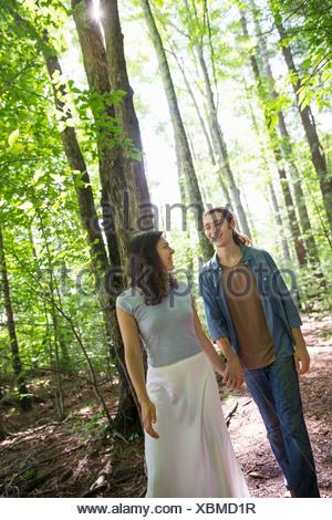 Dos personas, una joven y un joven, caminando lado a lado en el bosque.