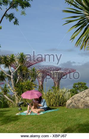 Madre e hija sentada bajo una sombrilla en Gardens by the Bay, Singapur