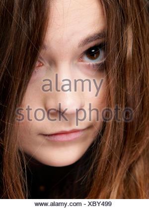 Close-up retrato de una bella mujer cubre el rostro por largos pelos marrones