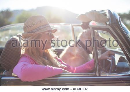 Mujer madura y perro en coche convertible