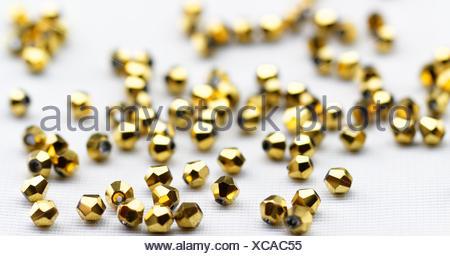Microesferas de vidrio dorado closeup sobre fondo blanco.