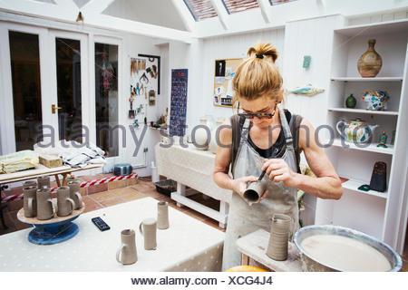 Un alfarero manejo de una olla de barro húmedo, suavizado de los bordes y prepararla para alimentación de hornos.