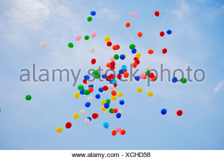 Coloridos globos de helio liberado en el cielo azul en una celebración Foto de stock