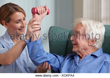 Cuidador ayudar a altos Hombre con pesas de mano