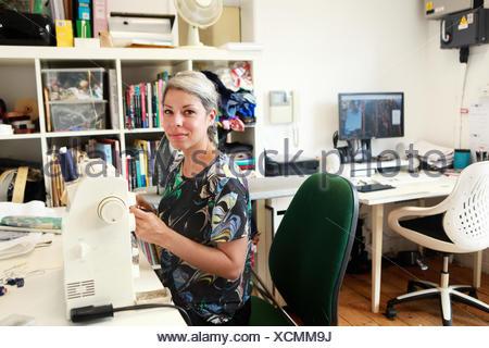 Diseñador que trabaja a máquina de coser en studio
