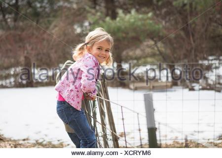 Joven escalando alambrada en el campo
