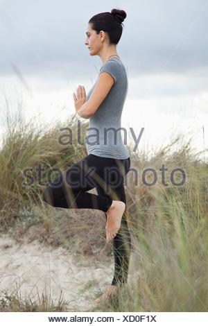 Mujer madura en la postura del árbol, sobre la playa, vista lateral