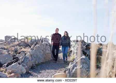 Vista frontal de la longitud completa de la joven pareja tomados de la mano caminando, mirando lejos Foto de stock