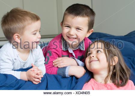 Hermanos jóvenes relajándose juntos en la cama