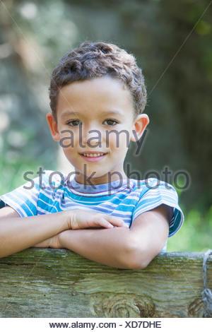 Retrato de niño recostado sobre la valla del jardín