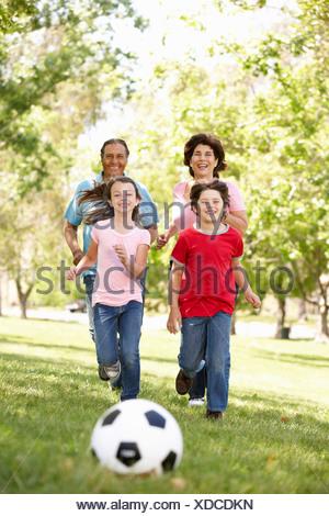 Jugando al fútbol en el parque de la familia