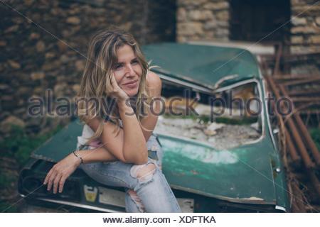 Mujer joven mirando a otro lado mientras está sentado en el automóvil abandonado