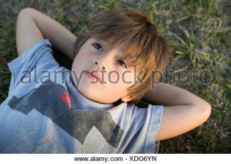Retrato de niño acostado sobre la hierba del parque mirando hacia arriba