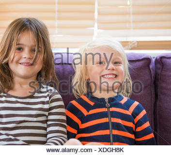 Retrato de chico y chica, sentada en un sofá, sonriendo