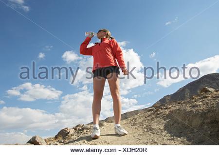 Emparejador femenino desde una botella de agua potable en las montañas