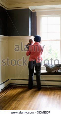 Madre sosteniendo bebé junto a la ventana Foto de stock
