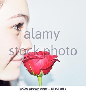 Close-up retrato de una adolescente oliendo una flor rosa