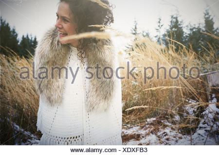 Mujer adulta media vistiendo cuello de piel en el bosque Foto de stock