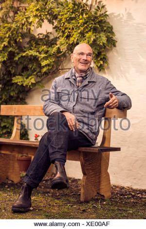 Hombre sentado en el banquillo Senior Foto de stock