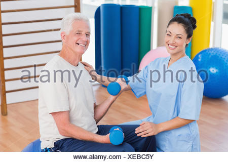 Instructora con altos hombre levantando pesas Foto de stock