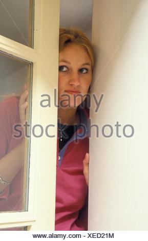 Mujer joven mirando sospechosamente fuera de la ventana