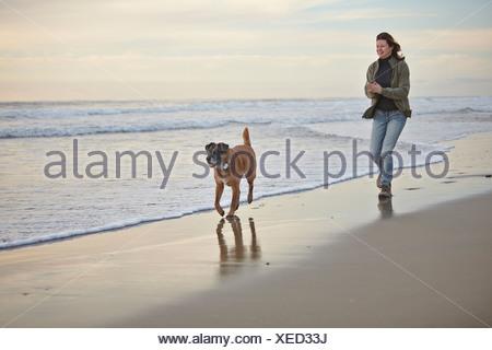 Mujer madura caminar perro en breezy beach
