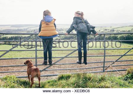 Dos niñas de pie en la puerta metálica