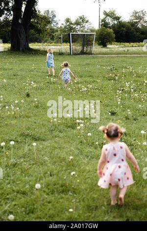 La qualité de mère ayant le temps de jeu drôle avec son bébé filles à un parc blowing dandelion - Jeune blonde - hippie filles porter des robes similaires avec Banque D'Images