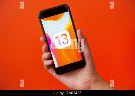 Kiev, Ukraine - le 19 septembre 2019: Studio shot of hand holding Apple iPhone 8 avec un fond d'abstrait de droit à propos de la sortie de la nouvelle iOS 13 Banque D'Images