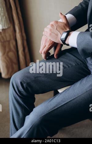Concepteur de réveil sur la main de l'homme d'affaires. Homme dans un costume gris est assis sur une chaise Banque D'Images