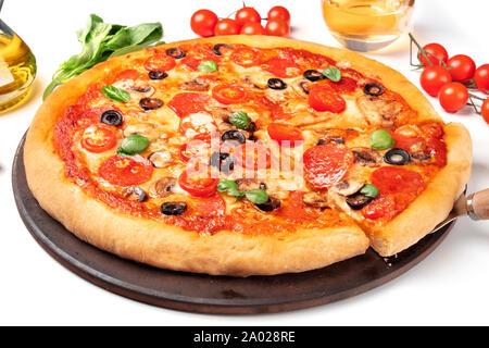 Pizza au pepperoni, salami, avec des tranches d'olives noires, des champignons, des feuilles de basilic frais et beaucoup de fromage Banque D'Images
