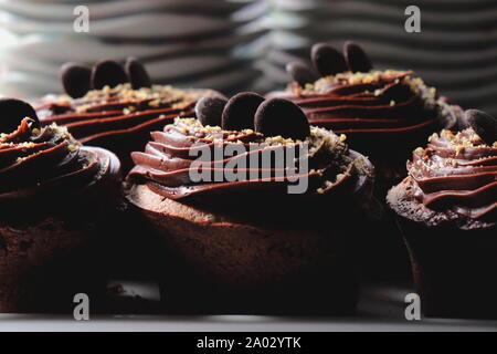 Muffins au chocolat noir garni de glaçage au chocolat, Close up, sucer les plaques dans l'arrière-plan