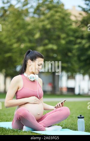 Jeune femme enceinte en vêtements rose assis sur les tapis d'exercice et à l'aide de téléphone mobile pendant l'entraînement sportif dans le parc Banque D'Images