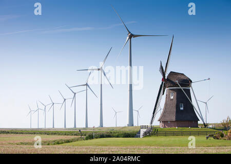 Ancien moulin à vent hollandais et des éoliennes modernes contre le ciel bleu en province néerlandaise de Groningue Banque D'Images