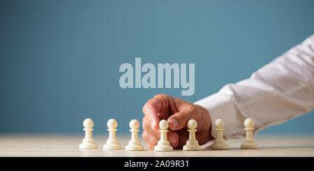 Main d'un pion blanc de positionnement d'affaires pièces des échecs sur un bureau sur fond bleu. Banque D'Images