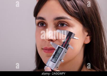 La mesure de fortes proportions de femmes médecin nez pendant l'utilisation d'étriers dans Clinic Banque D'Images