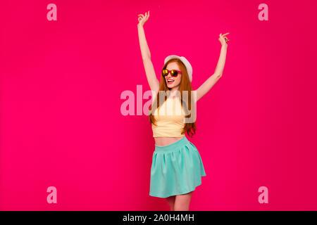 Beau mignon adorable attrayant fille gracieuse joyeuse fille rousse avec de longs cheveux d'or, le port de casquettes, des verres de couleur, jupe courte, sensibilisation han Banque D'Images