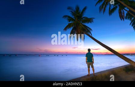 Silhouette traveler homme debout en face de la mer en admirant le coucher du soleil à côté de l'arbre de la noix de coco Banque D'Images