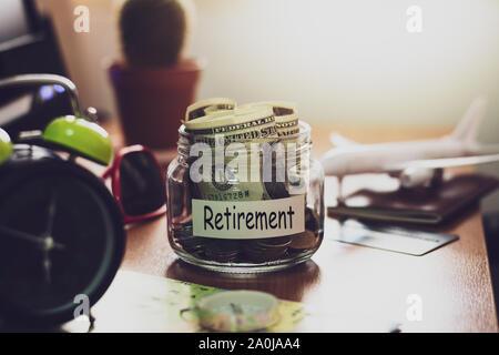 Concept de budget de retraite. De l'argent pour l'épargne-retraite dans un bocal en verre avec boussole, passeport, horloge, carte de crédit, d'aéronefs de jouets et de carte du monde sur worki Banque D'Images