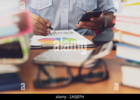 L'homme est à l'aide de téléphone mobile et le travail avec pile de documents sur Office 24, homme d'affaires est l'analyse marketing avec tableau de statistiques, d'affaires et O Banque D'Images