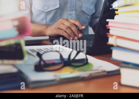L'homme est à l'aide d'ordinateur portable et travailler avec pile de documents sur Office 24, homme d'affaires est l'analyse marketing avec tableau de statistiques, d'entreprise et de bureau