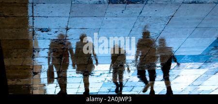 Réflexion floue silhouette d'ombre sur les trottoirs de la ville de personnes mystérieuses de marche la nuit, low angle view Banque D'Images