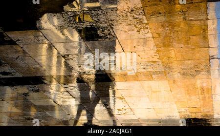 Silhouette d'ombre floue résumé réflexions de deux personnes marchant sur la chaussée de la rue ville humide Banque D'Images