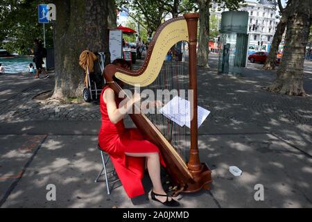 Zurich, Suisse,19 Juillet, 2019: belle fille élégante en robe rouge jouant sur la harpe dans la rue Park, extérieur, musicien de rue près de dame du lac de Zurich Banque D'Images