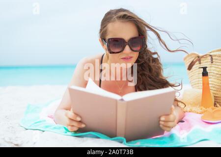 40 ans, femme, et élégant avec de longs cheveux bouclés dans un élégant maillot noir sur une plage blanche livre de lecture. Banque D'Images