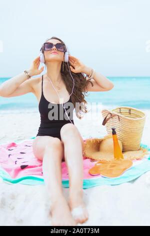 De 40 ans à la mode décontractée femme aux longs cheveux bouclés en noir élégant maillot de bain sur une plage de sable blanc se détendre tout en étant assis sur la pastèque ronde serviette. Banque D'Images