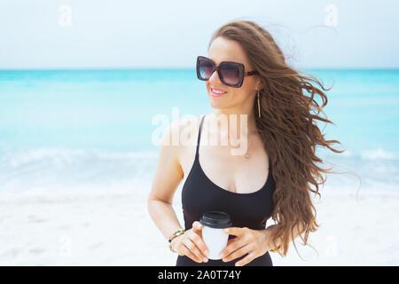 L'âge moyen élégant sourire femme aux longs cheveux bouclés en maillot noir élégant avec une tasse de café sur une plage de sable blanc. Banque D'Images